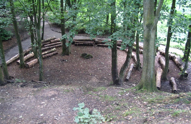 Image: Wooded area with logs laid out like benches