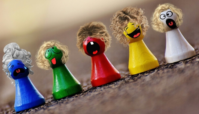 Image: painted wooden peg people in wigs and with different faces