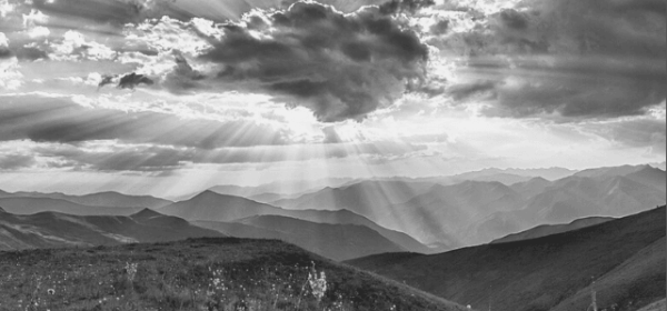 Featured Images - Black and white photo of a landscape featuring hills, meadow and sunlight streaming behind the clouds. Image from Pixabay