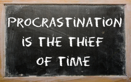 "Proverb ""Procrastination is the thief of time"" written on a blac"