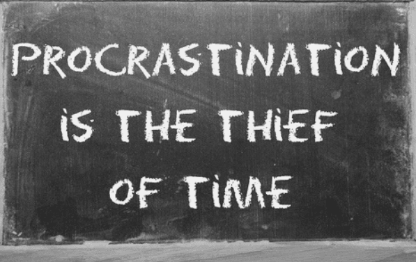 "Featured Images - Chalkboard with the words ""Procrastination is the thief of time"" written on"