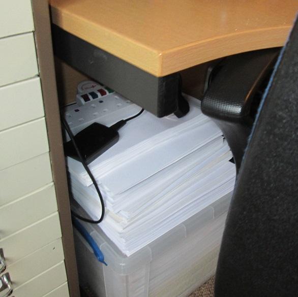 Image: Ari Meghlen's writing desk. Stack of scrap paper under the desk