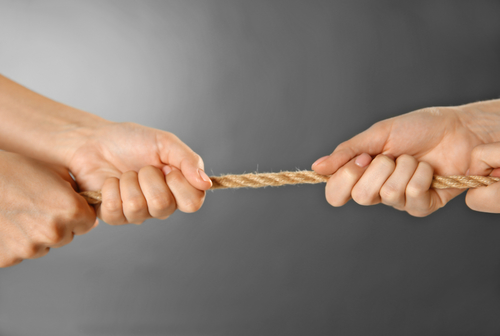 Image: Two pair of hands pulling on a rope against each other.
