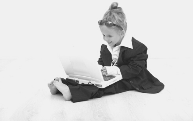 Featured Images - Photo of a little girl, dressed in a business suit, sunglasses and working on a laptop. Image bought from DepositPhotos