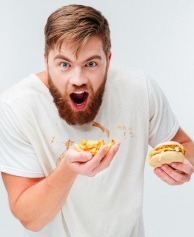 Hungry bearded man in filthy shirt eating hamburgers