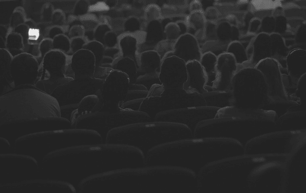 Featured Images - Photo of a large group of people sitting in a theatre.