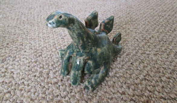 pottery sculpture of a stegosaurus sitting