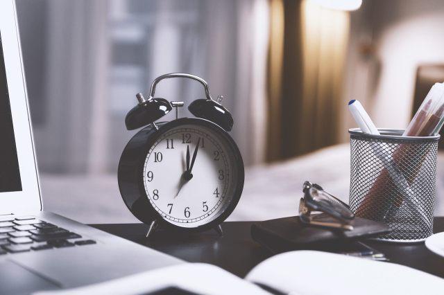 Time management. Image of alarm clock on a desk beside a laptop