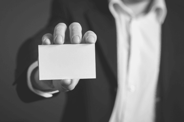 Featured Images - Man holding out a business card. Using business cards in your marketing