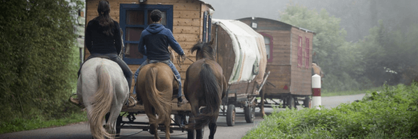 Image: Wooden gypsy caravans and horse riders