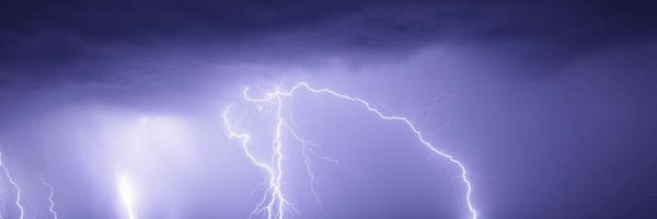 Image: Purple sky lit by lightning strike. Lightning storm