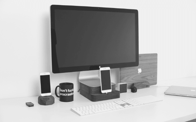 Featured Image - monitor screen, mobile phone and a cup with Dont fucking procrastinate on a desk.