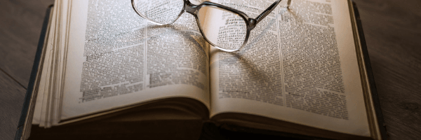 Title Image: Research category header.  Image: Open book with glasses on top