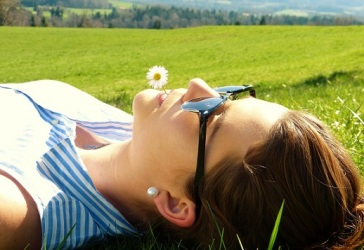 Woman lying in a meadow, relaxing.  Picture from Pixabay
