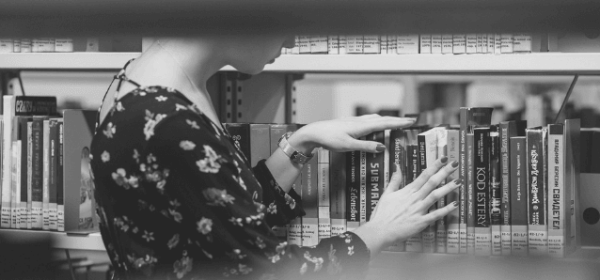 Featured Images - Woman browsing through books in a library
