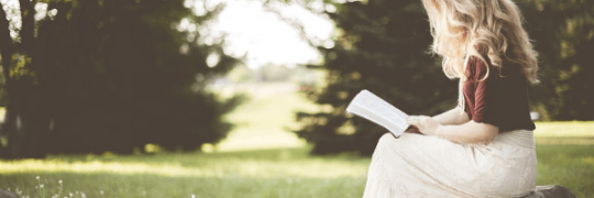 Young blonde woman reading in a field.  Image from Pixabay