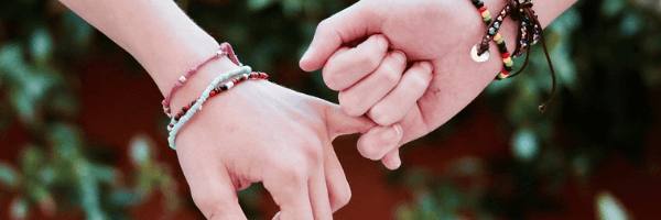 Image of two hands holding pinky fingers.  Friendship