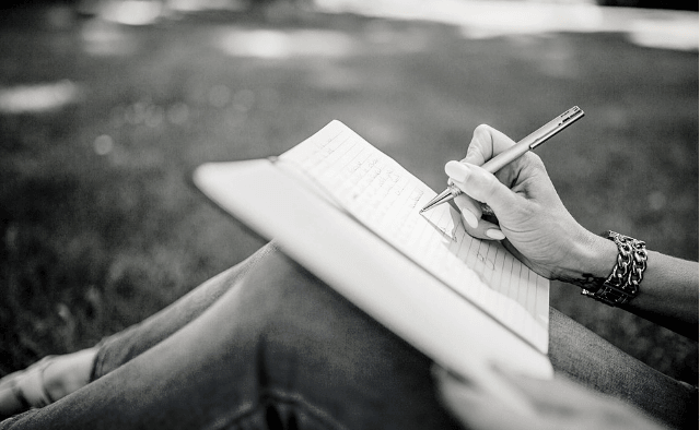 Featured Images - Image of a woman's hand writing in a notepad resting on her knee. Image from Pixabay