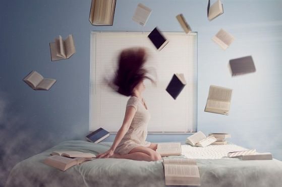 Woman sat on bed surrounded by flying books.  Image of Pixabay