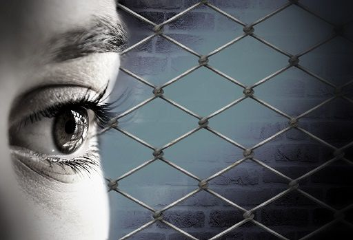 Woman imprisoned. Day of the Imprisoned Writer. Close up of a woman's eye with prison fencing behind.