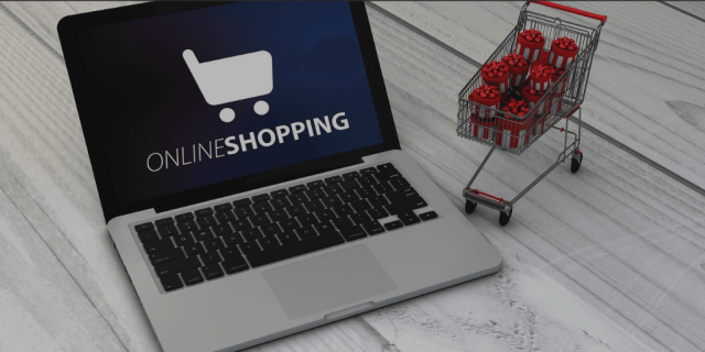 "Blog Image - Laptop with ""online Shopping"" written across the screen. Small shopping cart full of presents. Ecommerce"
