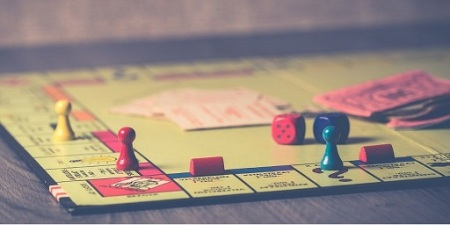 Blog Image - Photo of the boardgame Monopoly, with several pieces on the board, cards, money and dice