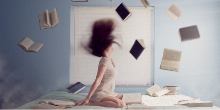 Blog Image - Woman knelt on a bed and books flying around her. Image from Pixabay
