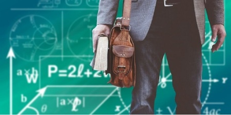 Blog Image - Cropped photo of a man holding a book, carrying a satchel and standing before a chalkboard covered in equations.  Image from Pixabay