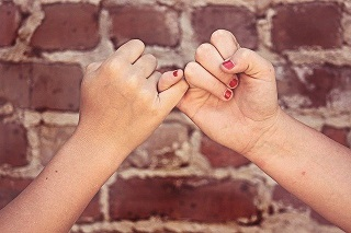 "Photo of two hands, with pinky fingers locked together in a ""pinky swear"". Image from Pixabay"