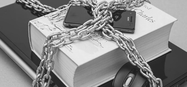 Featured Images - Photo of laptop, book and mobile phone in a stack, all chained. Protect your data.