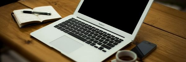 Laptop on desk beside an open notebook, pen, coffee cup and phone.  Image from Pixabay