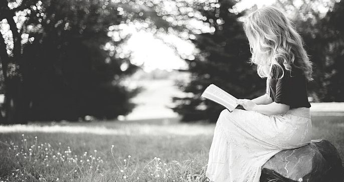 Featured Image - Woman sitting on a rock in a field reading a book. Image from Pixabay