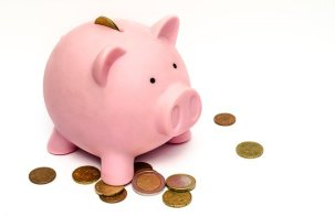 Piggy bank, pink pig with coins on the ground